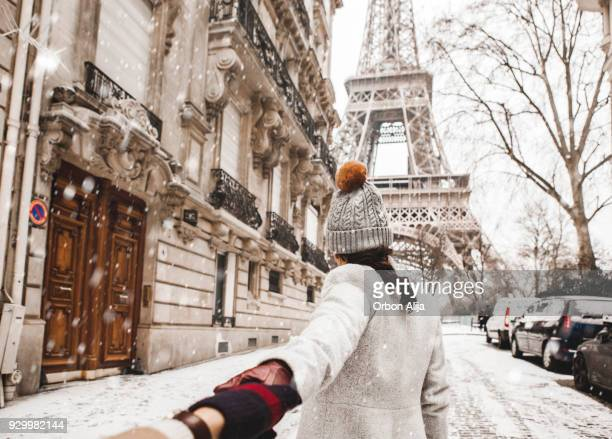 woman walking to the eiffel tower with snow - winter stock pictures, royalty-free photos & images