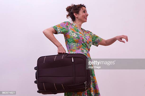 Woman walking to the right with a suitcase.