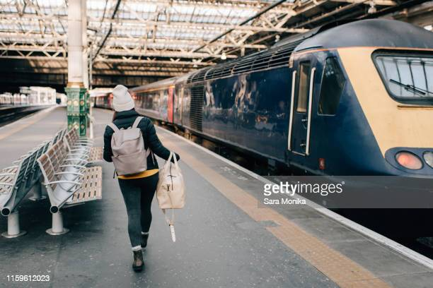 woman walking to train at platform, edinburgh, scotland - rear view stock pictures, royalty-free photos & images