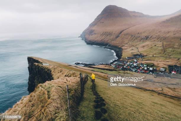 mulher que anda à vila perto do beira-mar em consoles de faroe - ilhas faeroe - fotografias e filmes do acervo