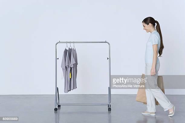 woman walking toward rack of tee-shirts, carrying shopping bags - 吊るす ストックフォトと画像