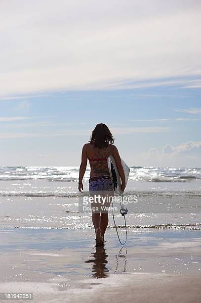 woman walking toward sea with surfboard. - dougal waters stock pictures, royalty-free photos & images