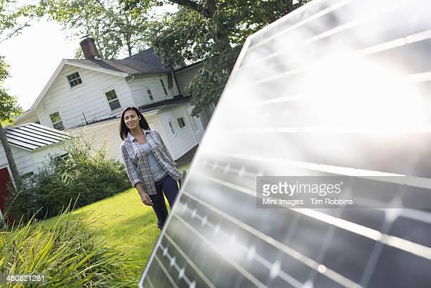 A woman walking towards a solar panel in a farmhouse garden.