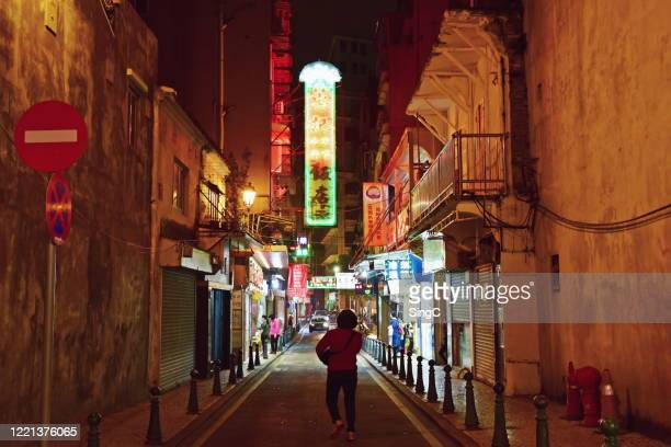a woman walking towards a street of neon lights in macau - macao stock pictures, royalty-free photos & images