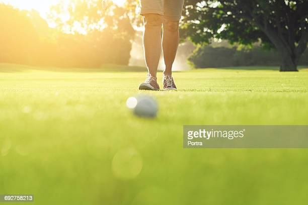 Woman walking towards golf ball on grassy field