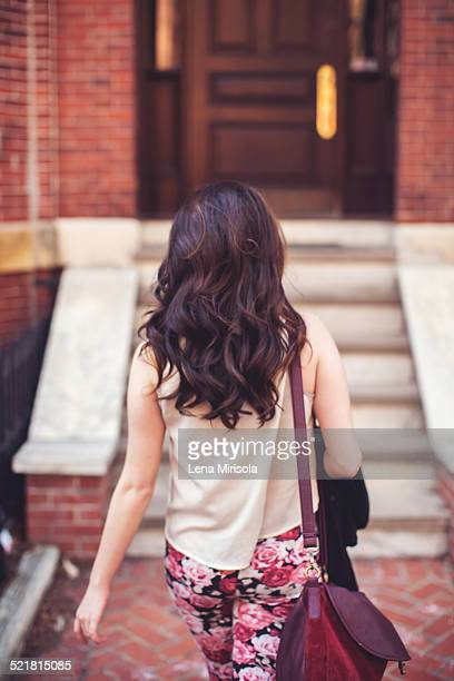Woman walking towards stairs to front door