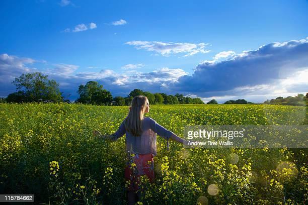 woman walking towards sunset in a field of rape