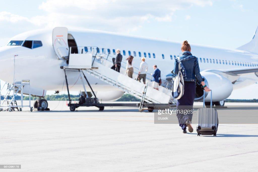 Woman walking towards the airplane : Stock Photo
