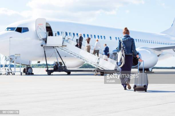 woman walking towards the airplane - aeroplane stock photos and pictures