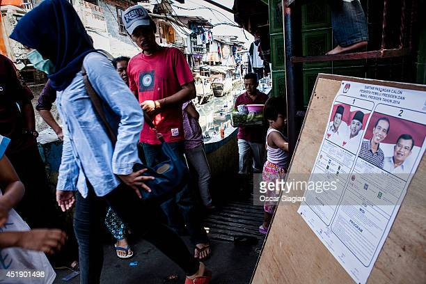 A woman walking trough the polling station after the the Indonesia presidential election his ballot on July 9 2014 in Jakarta Indonesia Election day...