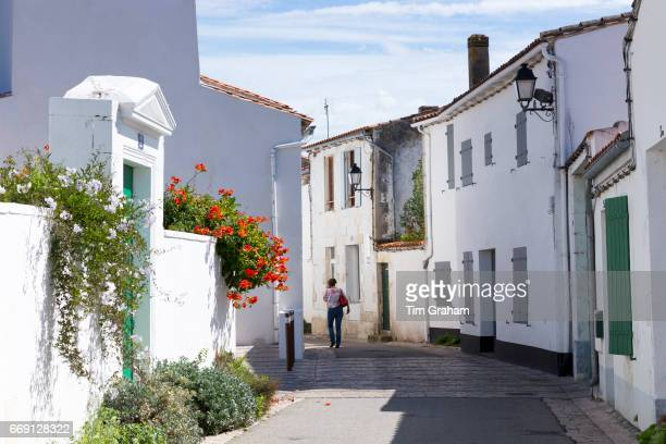 Woman walking typical street scene quaint houses traditional architecture on September 12 2015 in Les Portes en Re Ile de Re France