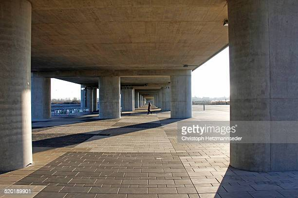 Woman walking under bridge