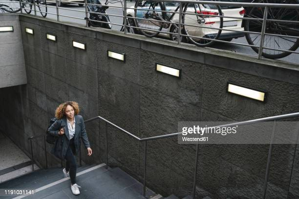 woman walking up dtairs at a subway station, berlin, germany - steps and staircases stock pictures, royalty-free photos & images
