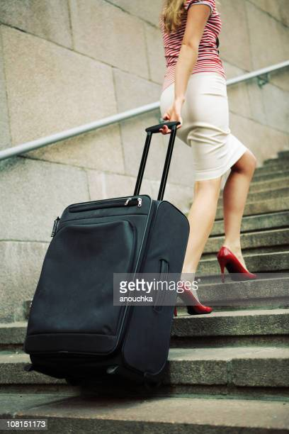 woman walking up outdoor stairs with rolling suitcase - wheeled luggage stock photos and pictures
