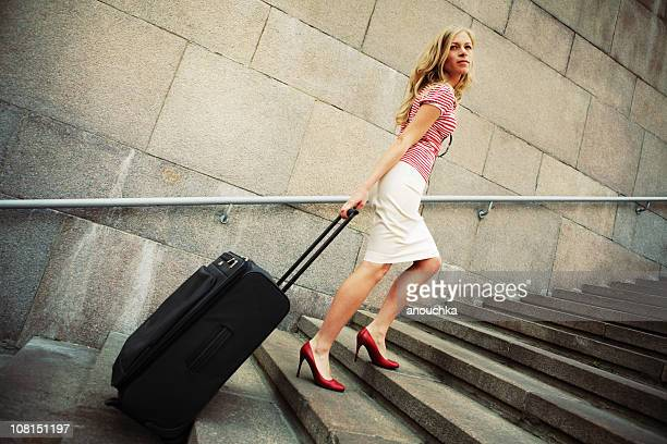 Woman Walking Up Outdoor Stairs with Rolling Suitcase
