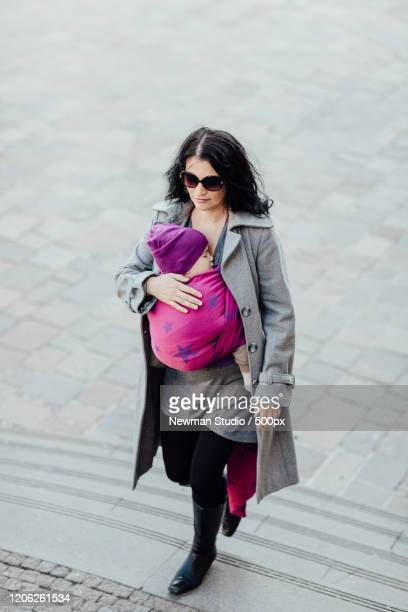 woman walking up stairs carrying baby (6-11 months) in woven wrap - 6 11 months stock pictures, royalty-free photos & images
