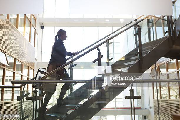 Woman walking up stairs in office building