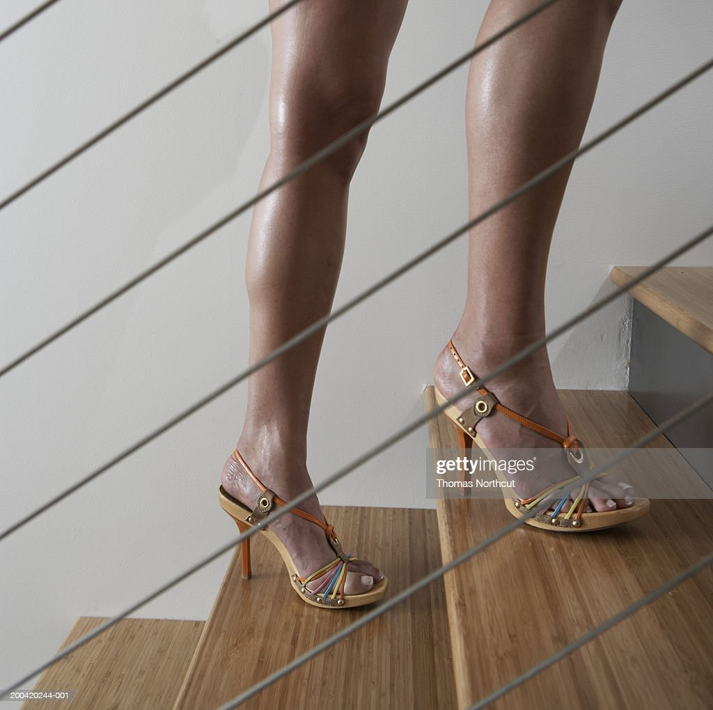 Woman walking up stairway, side view, low section : Stock Photo