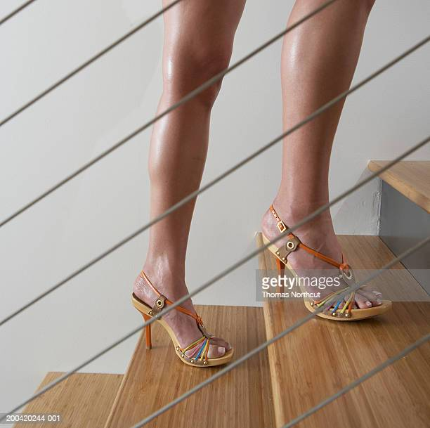 Woman walking up stairway, side view, low section