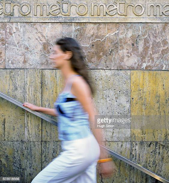 woman walking up steps with metro sign - hugh sitton stock-fotos und bilder