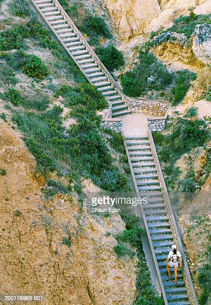 Woman walking up stone steps, elevated view