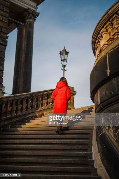 a woman walking up the stairs in winter - isolated color stock pictures, royalty-free photos & images