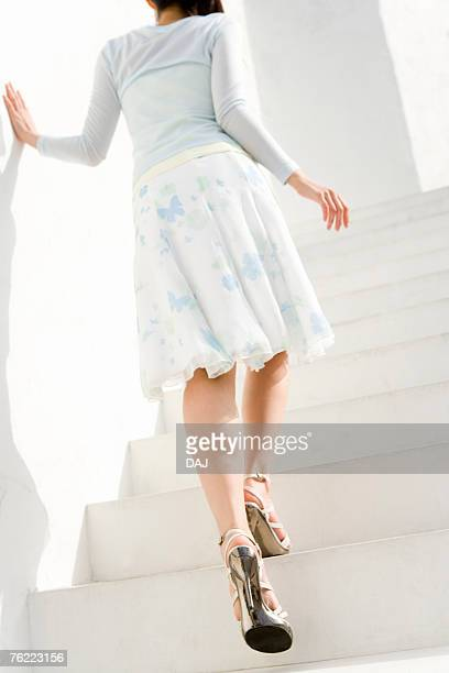A woman walking up the stairs, rear view, low angle view