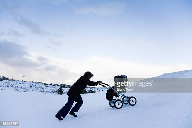 A woman walking uphill with a pram in the snow.