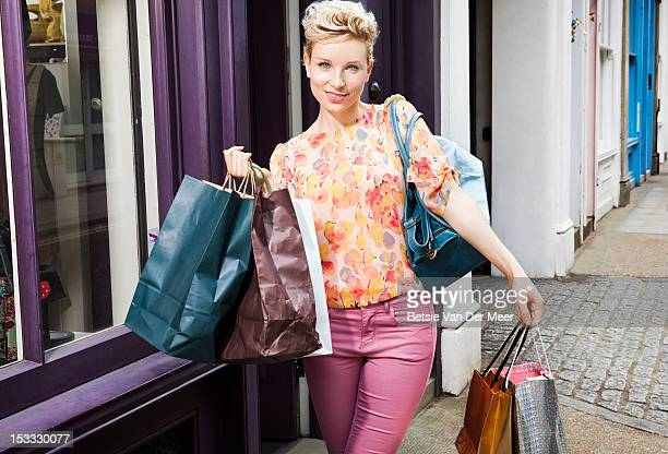 Woman walking with a lot of shopping bags.