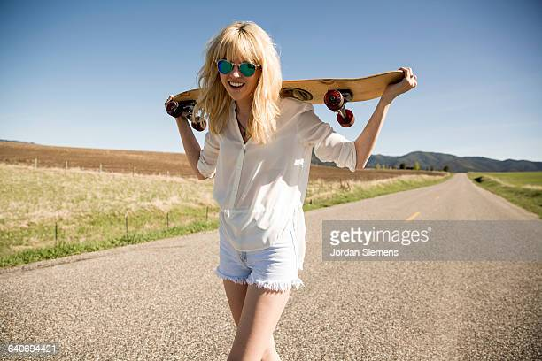 A woman walking with a skateboard.