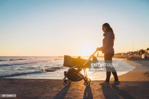 Woman walking with a stroller on the seashore at sunset