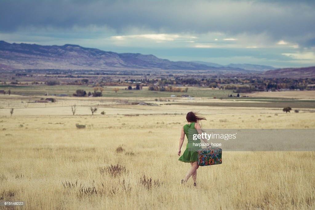 Woman walking with a suitcase searching for home. : Stock Photo