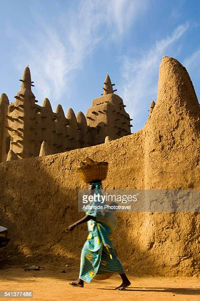 woman walking with baby in front of mosque of djenne - femme mali photos et images de collection
