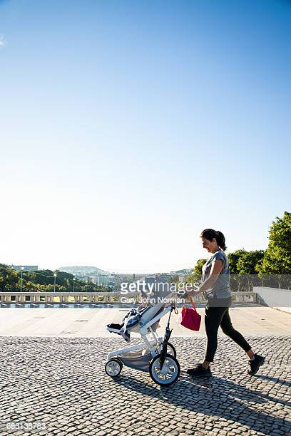 Woman walking with baby in stroller in Lisbon