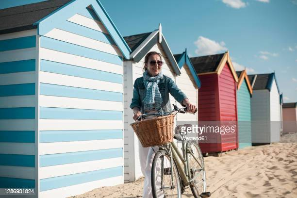 woman walking with bicycle on sand by beach huts on sunny day - beach stock pictures, royalty-free photos & images