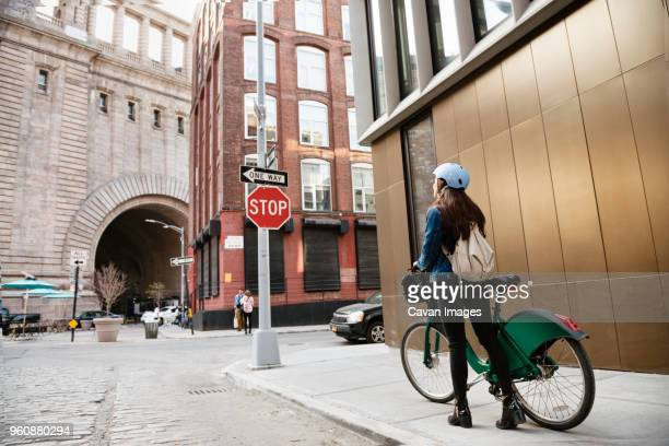 Woman walking with bicycle on sidewalk by building in city