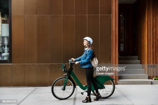 Woman walking with bicycle on sidewalk by building