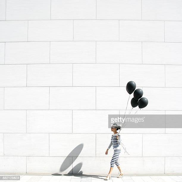 Woman walking with black balloons