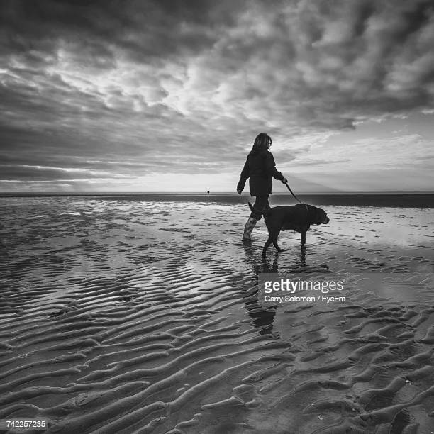 Woman Walking With Dog At Beach Against Cloudy Sky