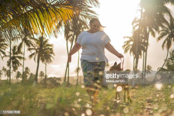 woman walking with dog at sunset - plus size model stock pictures, royalty-free photos & images