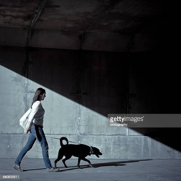 Woman walking with dog under bridge