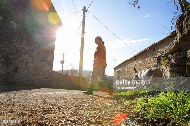 A woman walking with her dog on the rural street in France