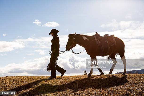 A woman walking with her horse.