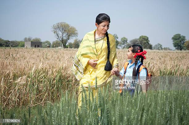 Woman walking with her schoolgirl in the field, Sohna, Haryana, India