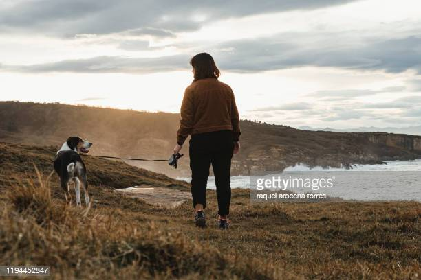 woman walking with his dog in a mountain during the sunset - オンダリビア ストックフォトと画像