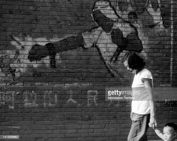 A woman walking with his son in front of a mural painting The painting is part of a campaign in favour of the liberation of the Arabic and African...