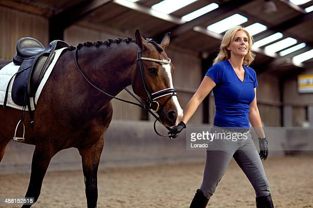 woman walking with horse indoors