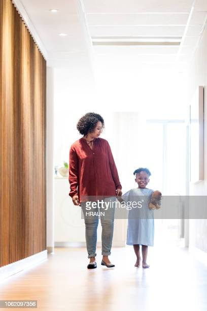 Woman walking with ill son in hospital corridor