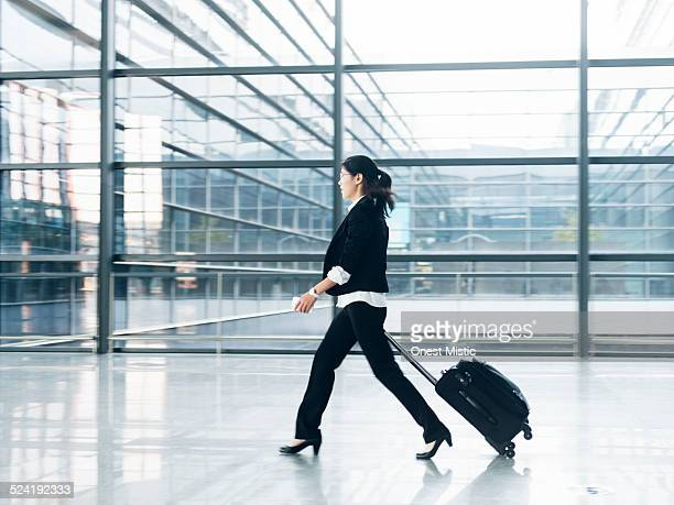 Woman walking with luggage at airport