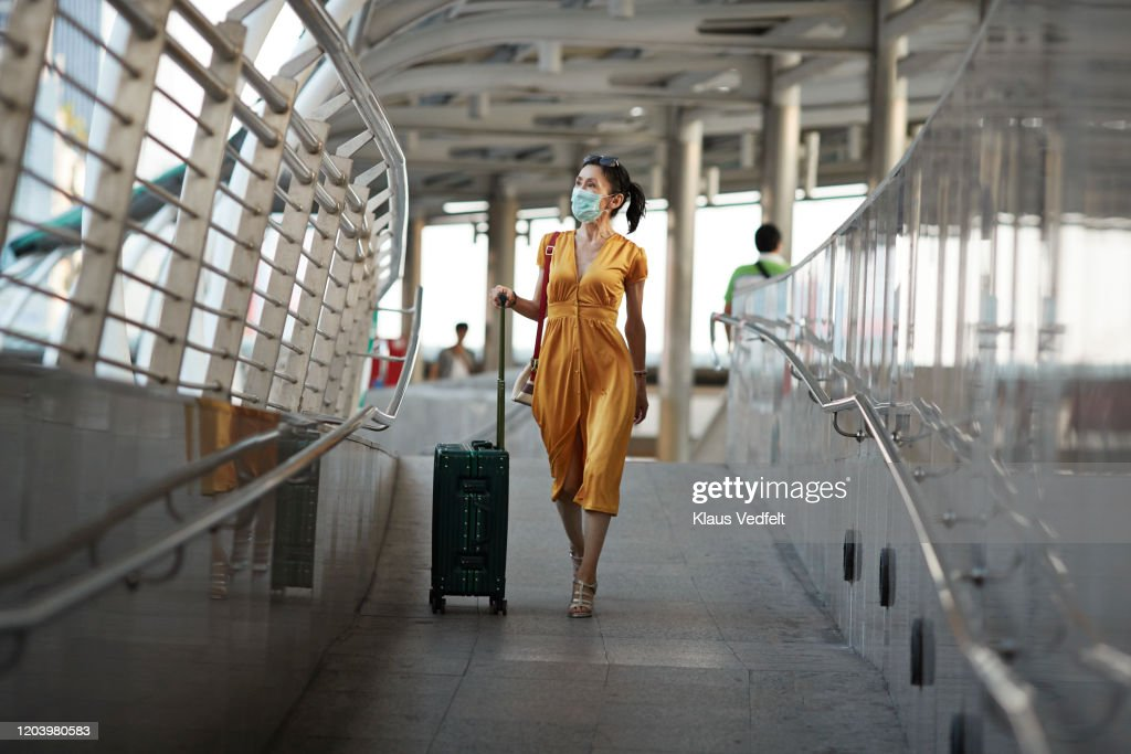 Woman walking with luggage at railroad station : Stockfoto